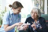 Nurse Advising Senior Woman On Medication At Home — Stock Photo