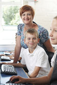 Male Elementary Pupil In Computer Class With Teacher — Stock Photo