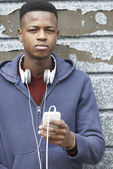 Teenage Boy Wearing Headphones And Listening To Music In Urban S — Stock fotografie