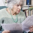 Senior Woman Going Through Bills And Looking Worried — Stock Photo #54983359