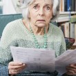 Senior Woman Going Through Bills And Looking Worried — Stock Photo #54983793