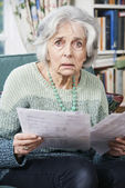 Senior Woman Going Through Bills And Looking Worried — Stock Photo