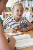 Elementary School Pupil Working At Desk In Classroom — Stock Photo