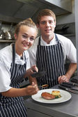 Chef Instructing Trainee In Restaurant Kitchen — Stock Photo