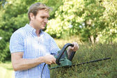 Man Cutting Garden Hedge With Electric Trimmer — Stock Photo