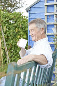 Senior Man Relaxing In Garden With Cup Of Coffee — Stock Photo