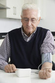 Senior Man Measuring Blood Pressure At Home — Stockfoto