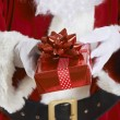 Close Up Of Santa Claus Holding Gift Wrapped Present — Stockfoto #57474855