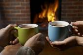 Couple With Hot Drink Relaxing By Fire — Stock Photo