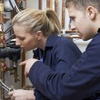 Female Trainee Plumber Working On Central Heating Boiler — Stock Photo #59456921