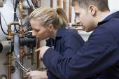 Female Trainee Plumber Working On Central Heating Boiler — Stock Photo