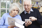 Senior Couple At Home With Bills Worried About Home Finances — Stock Photo