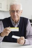 Senior Man Reading Information On Drug Packaging — Stock Photo