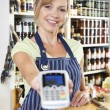 Sales Assistant In Food Store Handing Credit Card Machine To Cus — Stock Photo #62682743