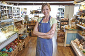 Owner Of Delicatessen Standing In Shop — Stock Photo