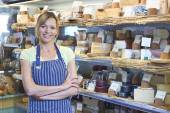 Owner Of Delicatessen Standing Next To Cheese Display — Stock Photo