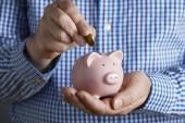 Man Putting Coin Into Piggy Bank — Stock Photo