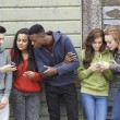 Group Of Teenagers Sharing Text Message On Mobile Phones — Stock Photo #62721071
