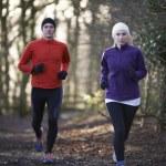 Couple On Winter Run Through Woodland — Stock Photo #64529409