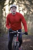 Man Riding Mountain Bike Through Woodlands — Fotografia Stock