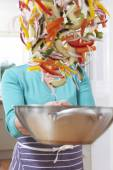 Female Cook Tossing Vegetables In Pan Obscuring Her Face — Stock Photo