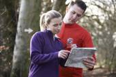 Couple Orienteering In Woodlands With Map And Compass — Stock Photo