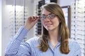Woman Trying On Glasses In Opticians — Stock Photo