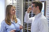 Optiker klient att ge råd om val av glasögon — Stockfoto