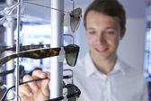 Człowiek wybiera okulary w sklepie — Zdjęcie stockowe
