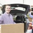 Couple Unloading New Television From Car Trunk — Stock Photo #68313639