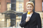 Female Journalist Broadcasting Outside Office Building — Stock Photo