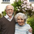 Senior Couple Standing Outside Pretty Cottage — Stock Photo #70406133