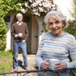 Senior Couple Standing In Cottage Garden With Coffee Cups — Stock Photo #70406671