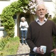 Senior Couple Standing In Cottage Garden Holding Coffee Cup — Stock Photo #70406841