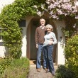 Senior Couple Standing Outside Pretty Cottage — Stock Photo #70408417