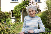 Senior Woman Standing Outside Pretty Cottage — Stock Photo