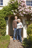 Retired Couple Standing Outside Pretty Cottage — Stock Photo