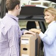 Couple Unloading New Television From Car Trunk — Stock Photo #70413669