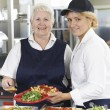 Portrait Of Two Dinner Ladies In School Cafeteria — Stock Photo #70426167