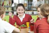 Group Of Pupils Sitting At Table In School Cafeteria Eating Lunc — Stock Photo
