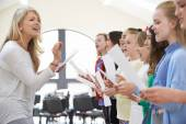 Children In Singing Group Being Encouraged By Teacher — Stock Photo