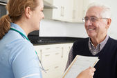 Nurse Discussing Medical Record With Senior Male Patient — Stock Photo