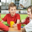 Group Of Pupils Sitting At Table In School Cafeteria Eating Meal — Stock Photo #71340253