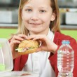 Girl Sitting At Table In School Cafeteria Eating Healthy Packed  — Stock Photo #71340295
