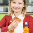 Girl Sitting At Table In School Cafeteria Eating Unhealthy Packe — Stock Photo #71340459