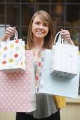 Alışveriş torbaları ile mutlu bir genç kadın portresi — Stok fotoğraf