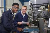 Engineer Showing Apprentice How to Use Drill In Factory — Stock Photo