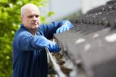 Man Clearing Leaves From Guttering Of House — Stock Photo