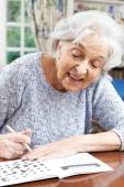 Senior Woman Relaxing With Crossword Puzzle At Home — Foto Stock