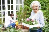 Teenage Granddaughter Helping Grandmother In Garden — Stock Photo